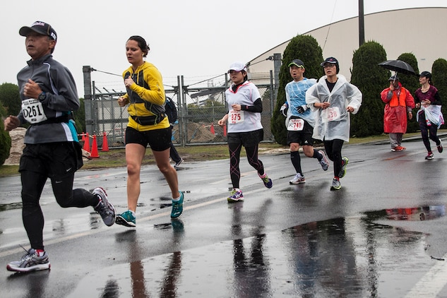 American and Japanese participants of the 2014 Kintai Marathon, which took place aboard Marine Corps Air Station Iwakuni, Japan, run past a puddle, April 13. The Kintai Marathon is one of the few annual events that give Japanese citizens an opportunity to come aboard station. Approximately 800 people signed up for the full marathon, half marathon and five-kilometer walk.