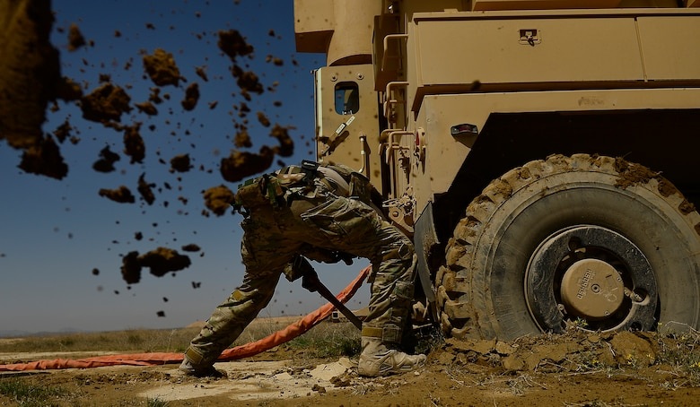 Staff Sgt. Kyle McGann digs mud from under a Mine Resistant Ambush Protected (MRAP) vehicle March 16, 2014, during demolition day at Kandahar Air Field, Afghanistan. McGann is a 466th Air Expeditionary Squadron, Explosive Ordnance Disposal technician. (U.S. Air Force photo/Staff Sgt. Vernon Young Jr.)