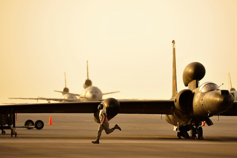 A member of the 380th Expeditionary Aircraft Maintenance Squadron assists in the removal of the temporary landing gear on a U-2 April 20, 2014, at a flightline in Southwest Asia. The U-2 utilizes temporary landing gear to reduce weight in flight. (U.S. Air Force photo/Tech. Sgt. Russ Scalf)