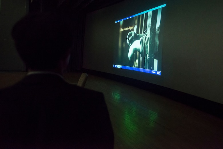 Shin Dong-hyuk, escapee of a North Korean interment camp, watches a video about prison camps during a presentation April 23, 2014, at Osan Air Base, Republic of Korea. Shin's story is featured in the book Escape From Camp 14 by Blaine Harden.