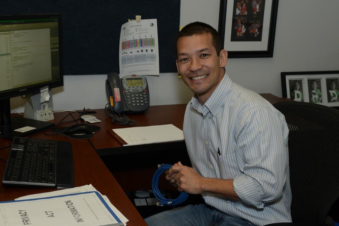 Tech. Sgt. Elijah Vo, a communication specialist,136th Airlift Wing, works on CAT V cable while wearing jeans in observance of 'Denim Day', a campaign observed annually on April 23 for the awareness of sexual assault prevention and response  at Naval Air Station Fort Worth Joint Reserve Base, Texas, April 23, 2014. This occasion marks the last event of the Sexual Assault Awareness Month in the Wing. (U.S. Air National Guard photo by Senior Master Sgt. Elizabeth Gilbert/Released)