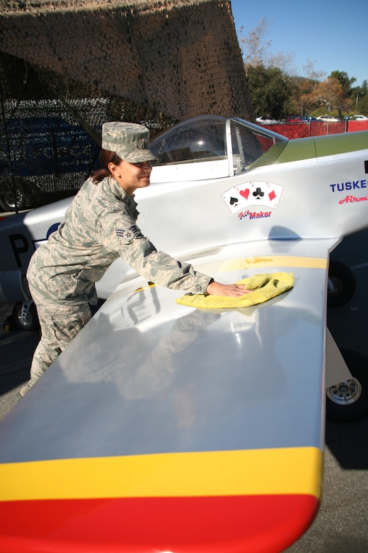 Senior Airman Paige McCann, a member of the 452d Communications Squadron, March ARB, polishes the right wing of a miniature P-51 Mustang aircraft on Dec. 31, 2013. McCann and other March airmen volunteered to educate the public about the WWII Tuskegee airmen and the P-51 Mustang aircraft during the 125th Pasadena Tournament of Roses Rose Parade Expo Village. (U.S. Air Force photo/Senior Airman Russell S. McMillan)