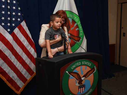 Tamara Parker, U.S. Central Command's Communication Integration directorate program manager, holds Dylan, son of Sgt. Fredrick J. Coleman, USCENTCOM public affairs, up to the lectern to let him see the camera and teleprompter at the media briefing display during USCENTCOM's Family Open House at MacDill Air Force Base, Fla., April 18. (U.S. Marine Corps photo by Sgt. Fredrick J. Coleman/Released)