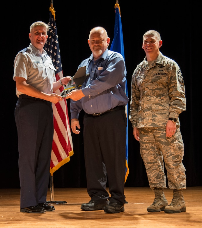 Col. Al Miller, 437th Airlift Wing vice commander (left), and Chief Master Sgt. Shawn Hughes, 437th AW command chief (right), present the Category II Civilian Award to Donald Norman, 437th Aerial Port Squadron load planning supervisor Apr. 24, 2014, at the Base Theater on Joint Base Charleston – Air Base, S.C. The Quarterly Awards are held to recognize outstanding Airmen, noncommisioned officers, senior noncomissioned officers, company grade officers and civilians for their hard work and dedication. (U.S. Air Force photo/ Airman 1st Class Clayton Cupit)