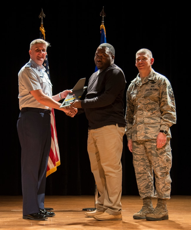 Col. Al Miller, 437th Airlift Wing vice commander (left), and Chief Master Sgt. Shawn Hughes, 437th AW command chief (right), present the Category I Civilian Award to Julius Murray, 437th Aerial Port Squadron hazardous cargo shipment inspector Apr. 24, 2014, at the Base Theater on Joint Base Charleston – Air Base, S.C. The Quarterly Awards are held to recognize outstanding Airmen, noncommisioned officers, senior noncomissioned officers, company grade officers and civilians for their hard work and dedication. (U.S. Air Force photo/ Airman 1st Class Clayton Cupit)