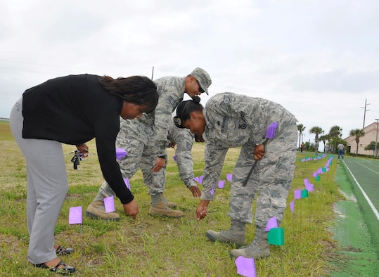 "Team Patrick-Cape volunteers place 1,046-marker flags near the track at Patrick Air Force Base, Fla., April 18, 2014, to symbolize the number of reported sexual assault victims in the Air Force in 2013. The 45th Space Wing hosted a ""Mile in her Shoes"" run-walk, in conjunction with other Sexual Assault Awareness events during April. (U.S. Air Force photo/Capt. Erin Dorrance)"