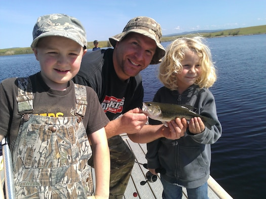 Future anglers pose with their first catch at Beale Air Force Base's Upper Blackwelder Lake, California. The Air Force recently partnered with the National Park Trust to bring the Buddy Bison Great Outdoors Challenge to military families at several installations. The program encourages children and families to spend less time in front of a screen and more time outdoors. (Courtesy photo)