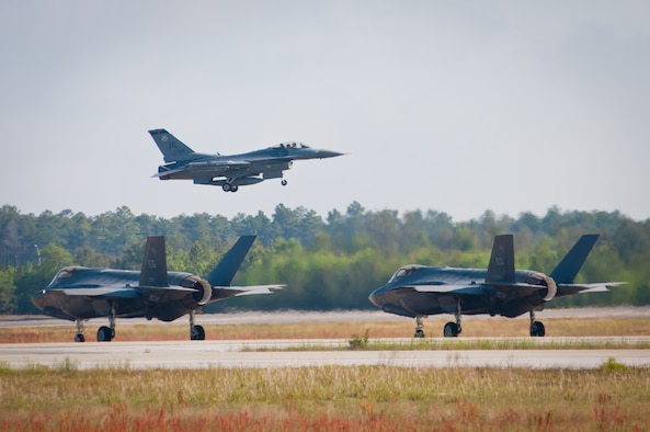 An F-16 Fighting Falcon takes off while two F-35 Lightning IIs taxi on the flightline in a training mission April 24, 2014, at Eglin Air Force Base, Fla. F-16s from the 419th and 388th Fighter Wings from Hill AFB, Utah, conducted their first training missions alongside the U.S. Air Force's newest fighter aircraft. (U.S. Air Force photo/Staff Sgt. Christina Judd)
