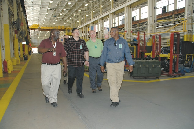 Todd Smith, safety supervisor, Production Plant Albany, Marine Depot Maintenance Command, (left) guides Marine Corps students from the U.S. Army Combat Readiness/Safety Center CP-12 Intern Training Program, Fort Rucker, Ala., on a tour of Production Plant Albany, April 4. The visit allowed the students to expand on what they heard in the classroom by seeing first-hand, workplace hazards, safety programs to mitigate those hazards and overall risk management processes.