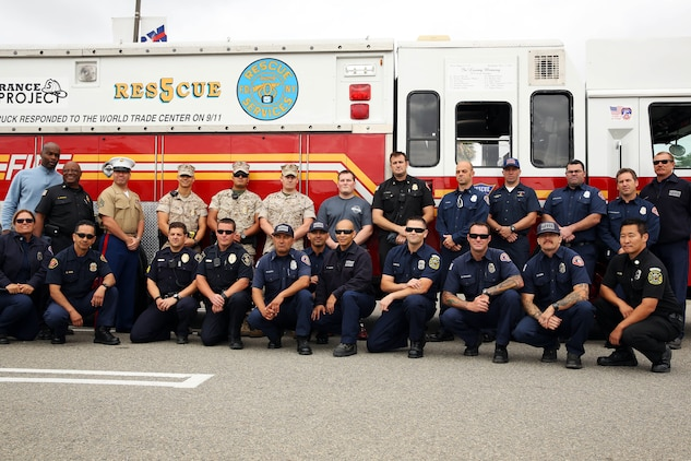 Members of the Remembrance Rescue Project, base firefighters from station three and five, and members of the Camp Pendleton Provost Marshalls Office gather in front of Rescue 5 during its visit to Camp Pendleton April 25. The Remembrance Rescue Project was created by firefighters to restore Rescue 4 and Rescue 5 as an educational effort for society, especially for those too young to remember the events of September 11. Rescue 4 and 5 are rescue engines used by New York emergency personnel during the events of September 11.