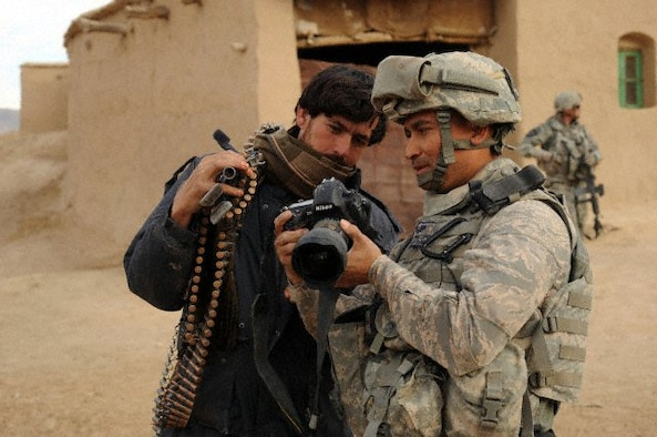 U.S. Air Force Tech. Sgt. Efren Lopez, 4th Combat Camera Squadron, shows digital photographs to an Afghan soldier in Shabila Kalan, Zabul province, Afghanistan. (courtesy photo)