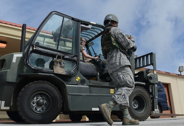 734th Air Mobility Squadron passenger service agents Senior Airman Tomas Cubilla and Airman 1st Class Adam McAteer operate a forklift April 16, 2014 during an operational readiness exercise on Andersen Air Force Base, Guam. The 36th Wing exercises regularly to ensure Airmen and the base populace are trained and ready to respond quickly and accurately in the event of a crisis. (U.S. Air Force photo by Airman 1st Class Emily A. Bradley/Released)