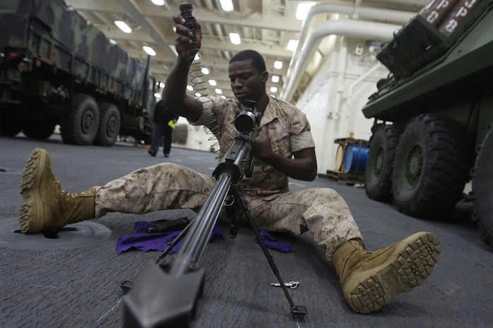 Lance Cpl. Vladimir Charles, a scout with 1st Light Armored Reconnaissance Battalion, 1st Marine Division, performs maintenance on the .50 caliber sniper rifle while part of Special Purpose Marine Air Ground Task Force ASEAN, aboard amphibious transport dock ship USS Anchorage (LPD-23), April 15, 2014. As part of SPMAGTF-ASEAN, 1st LAR showcased their territorial defense capabilities alongside units with 1st MLG on their mission to support the U.S. Secretary of Defense Chuck Hagel, during the Association of Southeast Asian Nations press conference in Hawaii, April 1-4, 2014. SPFMAGTF-ASEAN conducted further training at sea starting April 7, 2014. Charles is from Brooklyn, N.Y. (U.S. Marine Corps photo courtesy of Lance Cpl. Shaltiel Dominguez/ Released)