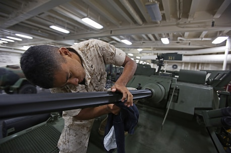 Lance Cpl. Jose Arredondo, a light armored vehicle crewman with 1st Light Armored Reconnaissance Battalion, 1st Marine Division, cleans the barrel of a 25mm Bushmaster chain gun while part of Special Purpose Marine Air Ground Task Force ASEAN, aboard amphibious transport dock ship USS Anchorage (LPD-23), April 15, 2014. As part of SPMAGTF-ASEAN, 1st LAR showcased their territorial defense capabilities alongside units with 1st MLG on their mission to support the U.S. Secretary of Defense Chuck Hagel, during the Association of Southeast Asian Nations press conference in Hawaii, April 1-4, 2014. SPFMAGTF-ASEAN conducted further training at sea starting April 7, 2014. Arredondo is from Reno, Nevada.