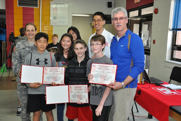 Kim Min-sung (front left), Kara Ohler, Jeremy Sumpter and Austin Barberree, pose with Far East District engineers as they accept their certificates for winning this year's toothpick bridge competition for best overall design.