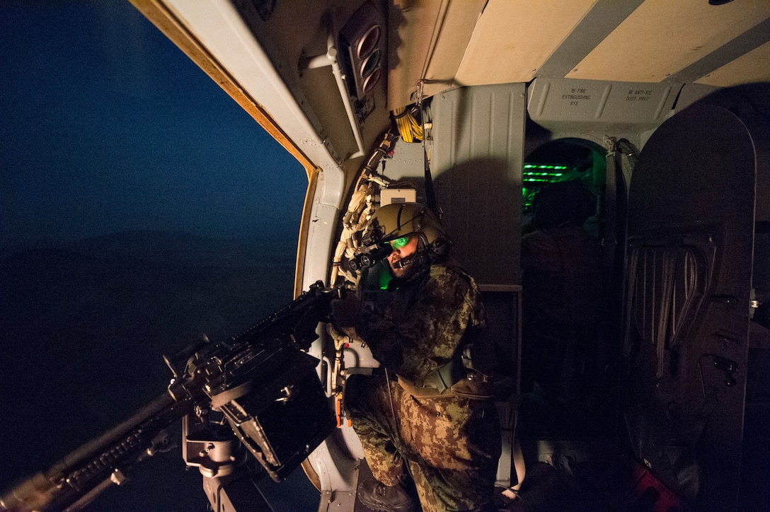 An Afghan air force Mi-17 aerial gunner fires an M-240 machine gun while flying over a weapons range March 13, 2014, near Kabul, Afghanistan. U.S. Air Force airmen from the 438th Air Expeditionary Wing/NATO Air Training Command-Afghanistan flew a night vision goggle training mission with an AAF aircrew to further increase the operational capability of the AAF. (U.S. Air Force photo/Tech. Sgt. Jason Robertson)