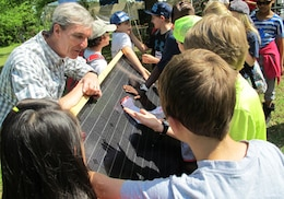 Jeff Waters, an instructor at Calhoun Community College's Clean Energy Center, explains solar technology using a solar panel during Earth Day April 24 at the Path to Nature. The students are from Horizon Elementary School.