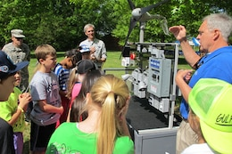Jerry Adams, an instructor at Calhoun Community College's Clean Energy Center, explains windmill technology using a wind turbine trainer during Thursday's Earth Day event at the Path to Nature. The students are from Horizon Elementary School.