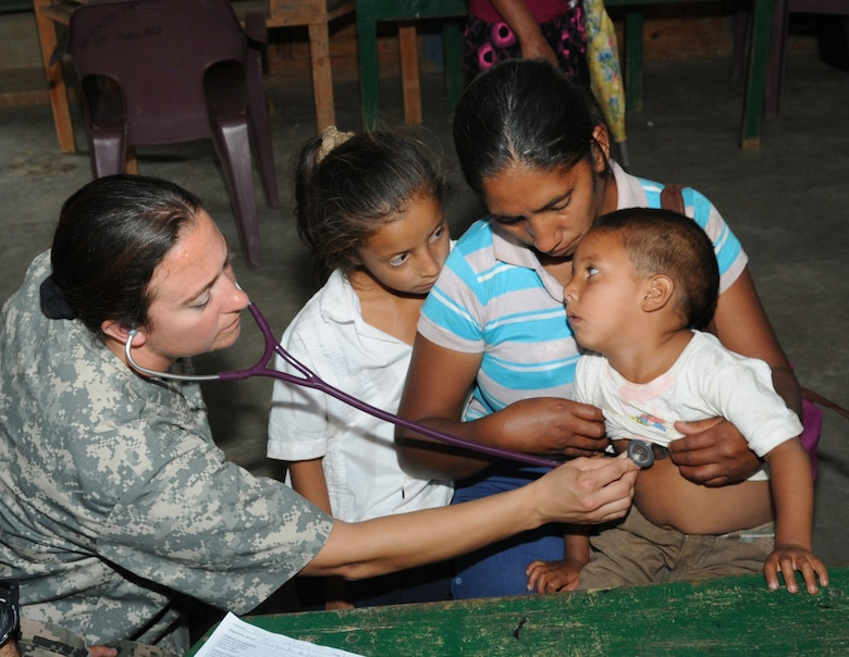 U. S. Army Capt. Emily Hollis listens to a Honduran child's heart while examining him during a Medical Readiness Training Exercise in El Naranjo, a remote village in the La Paz region of Honduras, April 24-25.  The Medical Element, with support from JTF-Bravo Joint Security Forces, partnered with the Honduran Ministry of Health, the Honduran National Police, and the Honduran military to provide medical care to nearly 1,000 people over a two day period.  The teams worked together to provide preventive medicine to their patients which included classes on hygiene, hand washing, preventive dental care, and nutrition.  They also provided immunizations to infants, dental care, well women screenings, wellness checkups, medications, and minor medical procedures.  (Photo by U. S. Air National Guard Capt. Steven Stubbs)