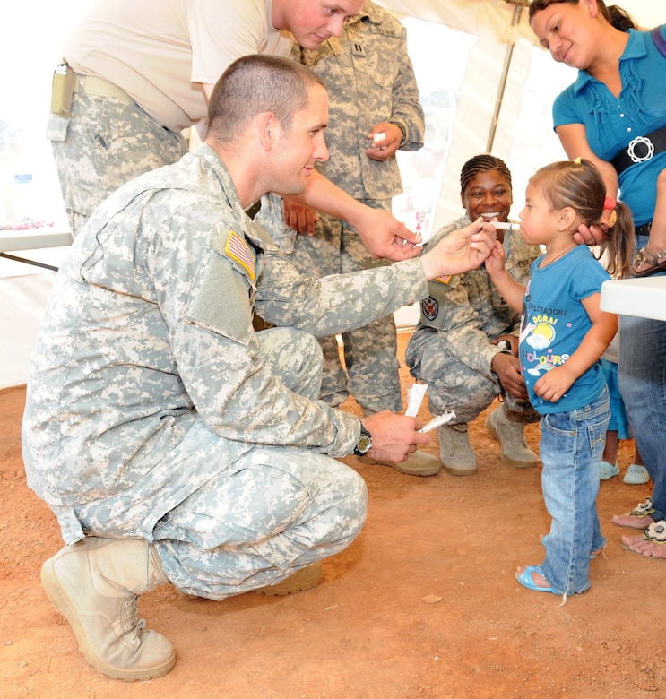 U. S. Army Spc. Liam Dooley gives a Honduran child medicine as part of the preventive medicine program during a Medical Readiness Training Exercise in El Naranjo, a remote village in the La Paz region of Honduras, April 24-25.  The Medical Element, with support from JTF-Bravo Joint Security Forces, partnered with the Honduran Ministry of Health, the Honduran National Police, and the Honduran military to provide medical care to nearly 1,000 people over a two day period.  The teams worked together to provide preventive medicine to their patients which included classes on hygiene, hand washing, preventive dental care, and nutrition.  They also provided immunizations to infants, dental care, well women screenings, wellness checkups, medications, and minor medical procedures.  (Photo by U. S. Air National Guard Capt. Steven Stubbs)