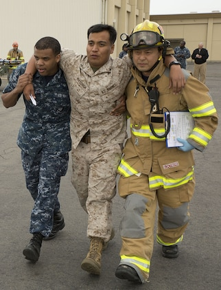 Seaman Darion Black, left, general duty corpsman with Robert M. Casey Medical and Dental Clinic, and a firefighter with the station Fire Department work together to assist Lance Cpl. David Mayorga, a patrolman with the Provost Marshal's Office, as part of a mock scenario during a mass casualty evacuation drill on the flight line aboard Marine Corps Air Station Iwakuni, Japan, April 2, 2014.