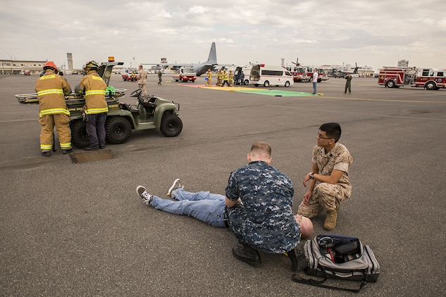 First responders from Robert M. Casey Medical and Dental Clinic, station Fire Department and the Provost Marshal's Office tend to role-players during a mass casualty evacuation drill on the flight line aboard Marine Corps Air Station Iwakuni, Japan, April 2, 2014. The scenario simulated a propane tank explosion from a food vendor in a highly populated area.