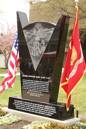 The 6-67 Memorial sits between the U.S. flag and the Marine Corps flag during the memorial's dedication at The Basic School on April 25, 2014. The memorial was dedicated to the class who suffered 50 casualties and more than 200 wounded Marines.