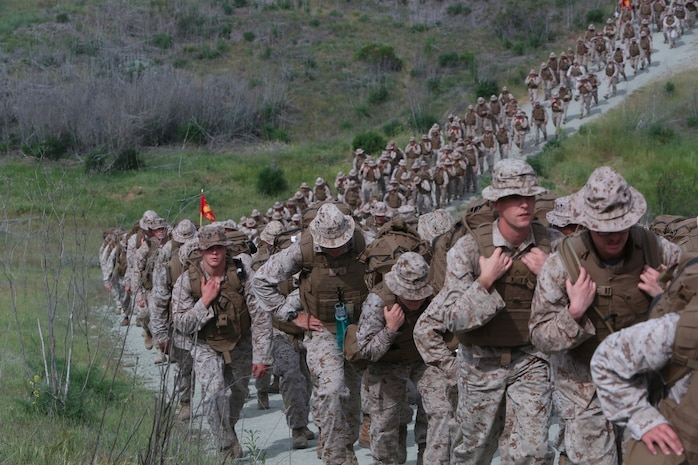 Marines with I Marine Headquarters Group push up a hill during a regimental hike conducted aboard Camp Pendleton, Calif., April 17, 2014. The Marines wore their flak jackets and carried weighted assault packs on the eight-mile conditioning hike. This hike was the second of a series in a series of conditioning events that aim to improve the Marines operational readiness and camaraderie.