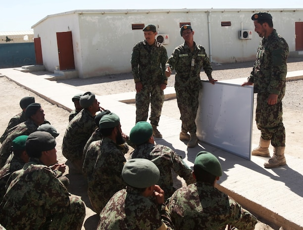 Instructors with 4th Tolai, 6th Kandak, 4th Brigade, 215th Corps, Afghan National Army, give soldiers a class on patrolling tactics during an exercise aboard Camp Shorabak, Afghanistan, April 19, 2014. The training exercise was designed to ensure the efficiency of the soldiers before they begin conducting perimeter patrols with Marines in the area surrounding Camps Bastion, Leatherneck, Shorabak complex. (Marine Corps photo by Cpl. Cody Haas/ released)