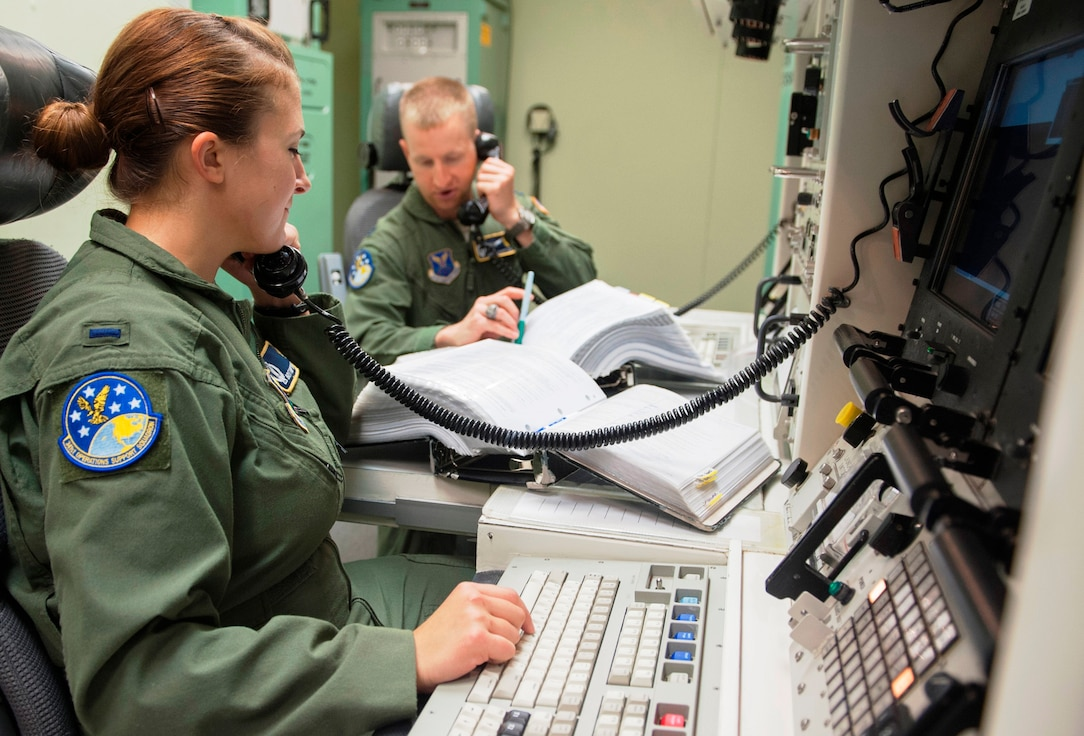 First Lt. Brittany Morton, left, and her missileer partner answer their phones during a trainer ride at the missile procedures trainer. Two missileers man a launch control center together and take turns sleeping so that one person is watching the LFs at all times. Morton is a 490th Missile Squadron missile combat crew commander. (U.S. Air Force photo/Beau Wade)
