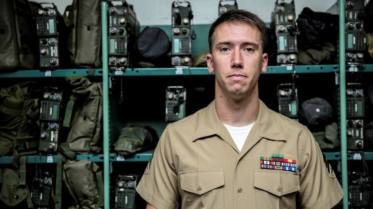 Sergeant Kristopher Golden, radio chief, 15th Marine Expeditionary Unit, poses for a photo in front of gear he is responsible for aboard Camp Pendleton, Calif., April 25, 2014. Golden, 27, is from Lacey, Wash.