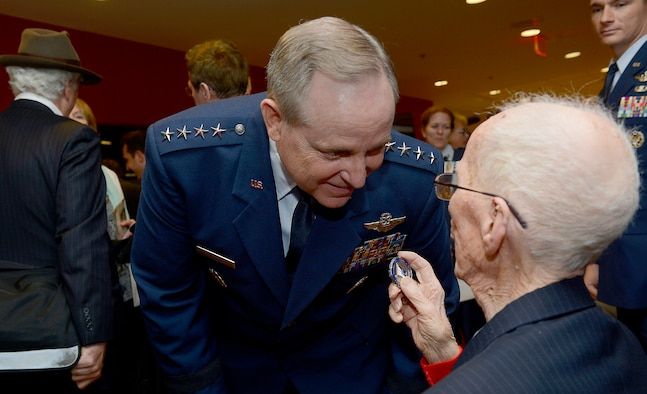 Air Force Chief of Staff Gen. Mark A. Welsh III congratulates 1st Lt. James Mahon after awarding him the Prisoner of War Medal during a ceremony April 30, 2014, at the Pentagon. Mahon and eight fellow World War II aviators, all bomber crew members, were shot down flying missions over Germany and were held in a prison camp in Wauwilermoos, Switzerland. The men were originally denied POW status. U.S. Army Maj. Dwight Mears, whose grandfather Lt. George Mears, who was held at the prison, fought diligently for 15 years to get the men recognized as POWs. (U.S. Air Force photo/Scott M. Ash)