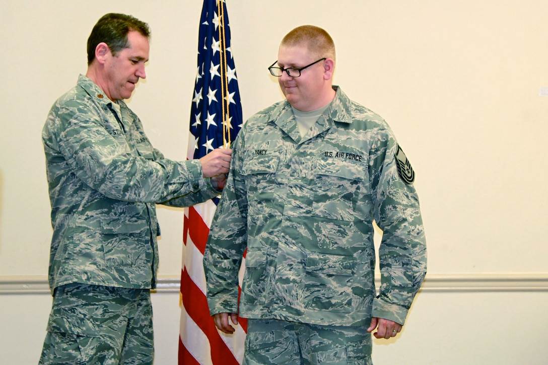 Tech. Sgt. Christopher Yancy, a mission capability technician for the 126th Supply Chain Management Squadron attached to the 126th Air Refueling Wing, receives his promotion to the rank of Master Sgt. from Maj. Doug Stuart, the Public Affairs Officer for the 126th Air Refueling Wing, while temporarily assigned to Joint Base Pearl Harbor-Hickam, Hawaii, April 15, 2014. Yancy was at Joint Base Pearl Harbor-Hickam, Hawaii as part of a training exercise with other members from the 126th Air Refueling Wing. The 126th Air Refueling Wing is attached to the Illinois Air National Guard, based out of Scott Air Force Base, Ill. (Courtesy photo)