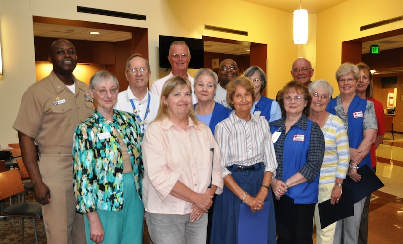 The American Red Cross volunteers at Naval Health Clinic Charleston were honored for their contributions during a recognition ceremony April 29, 2014, at the clinic on Joint Base Charleston – Weapons Station. NHCC currently has 18 American Red Cross volunteers who donate approximately 4,500 hours of service annually. Back row: NHCC Commanding Officer Capt. Marvin Jones, William Mehard, James Crane, Stanley Nelson, James Tyrrell, Jeanne Carmichael; center row: Eileen Hadbabny, Reggie Gardner, Paulette Blew, Barb Tyrrell, Cheryl Harris; front row: Lois Neal, Carol Cramer, Sharon Monheit. (U.S. Navy photo/Kris Patterson)