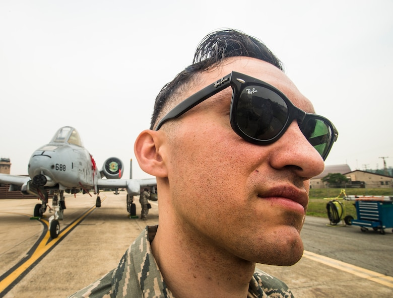 Senior Airman Juan Gonzalez, a 25th Aircraft Maintenance Unit weapons load crew member, reflects on his team's victory in front of their A-10 during the 2014 Korean Peninsula Weapons Loading Competition April 26, at Osan Air Base, Republic of Korea. Gonzalez, and his team members, Senior Airmen, Jacob Jennings and Chandler Rickard, will go on to compete at higher levels. (U.S. Air Force photo by Staff Sgt. Jake Barreiro)