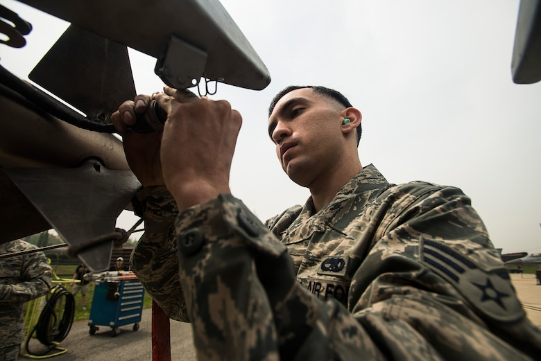 Senior Airman Juan Gonzalez, a 25th Aircraft Maintenance Unit weapons load crew member, secures a missle on an A-10 during the 2014 Korean Peninsula Weapons Loading Competition April 26, 2014, at Osan Air Base, Republic of Korea. The 25th AMU's team loaded weapons on an A-10, while the other three teams loaded F-16s. (U.S. Air Force photo by Staff Sgt. Jake Barreiro)