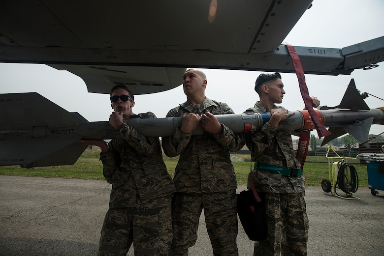 The 25th Aircraft Maintenance Unit weapons load crew team carries a missle to an A-10 during the 2014 Korean Peninsula Weapons Loading Competition April 26, at Osan Air Base, Republic of Korea. The 25th AMU's team consisted of Senior Airmen Chandler Rickard, Jacob Jennings and Juan Gonzalez. (U.S. Air Force photo by Staff Sgt. Jake Barreiro)
