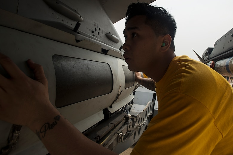 Senior Airman Ryanted Duarte, an 80th Aircraft Maintenance Unit weapons load crew member at Kunsan Air Base, Republic of Korea, guides a missle onto an F-16 during the 2014 Korean Peninsula Weapons Loading Competition April 26, at Osan Air Base. The 35th AMU from Kunsan AB and 36th and 25th AMU from Osan AB also competed. (U.S. Air Force photo by Staff Sgt. Jake Barreiro)