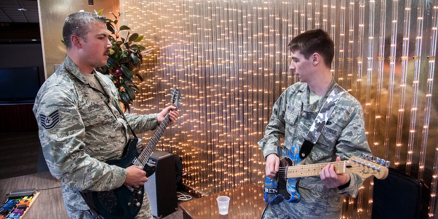 PETERSON AIR FORCE BASE, Colo. -- Airman 1st Class Brett Wells, 21st Communications Squadron (right) and Tech. Sgt. Andrew Decker, 21st Aerospace Medicine Squadron, participate in a guitar duel at The Club April 25. The duel was part of the Wing's monthly Final Friday event. (U.S. Air Force photo/Craig Denton)