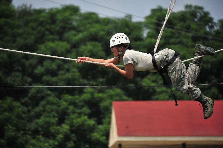 A Commissioned Officer Training School student pulls herself across a rope July 24, 2014, during an exercise conditioning course at Maxwell Air Force Base, Ala. Commissioned medical, legal and chaplain officers must go through COT to receive military leadership training. The ropes course is a confidence and team building part of the training. (U.S. Air Force photo/Staff Sgt. Natasha Stannard)