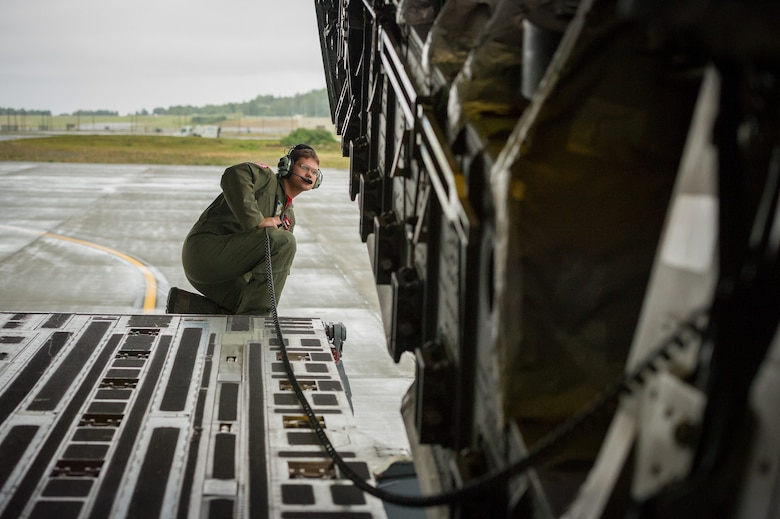Staff Sgt. Joe Braunwarth kneels on the ramp aboard a C-17 Globemaster III July 25, 2014, during parking operations for Arctic Thunder Open House 2014 at Joint Base Elmendorf-Richardson, Alaska. Arctic Thunder, a biennial event, features more than 40 Air Force, Army and civilian aerial acts. It is the largest two-day event in the state and one of the premier aerial demonstrations in the world. Braunwarth is a loadmaster with the 517th Airlift Squadron. (U.S. Air Force photo/Master Sgt. John R. Nimmo Sr.)