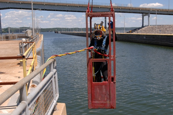 Diver Dustin Kelley, Nashville District Dive Team, is lowered into Pickwick Lock in Counce, Tenn., to inspect the lock gate and miter seal after the gate shook and experienced a malfunction early in the morning July 28, 2014.