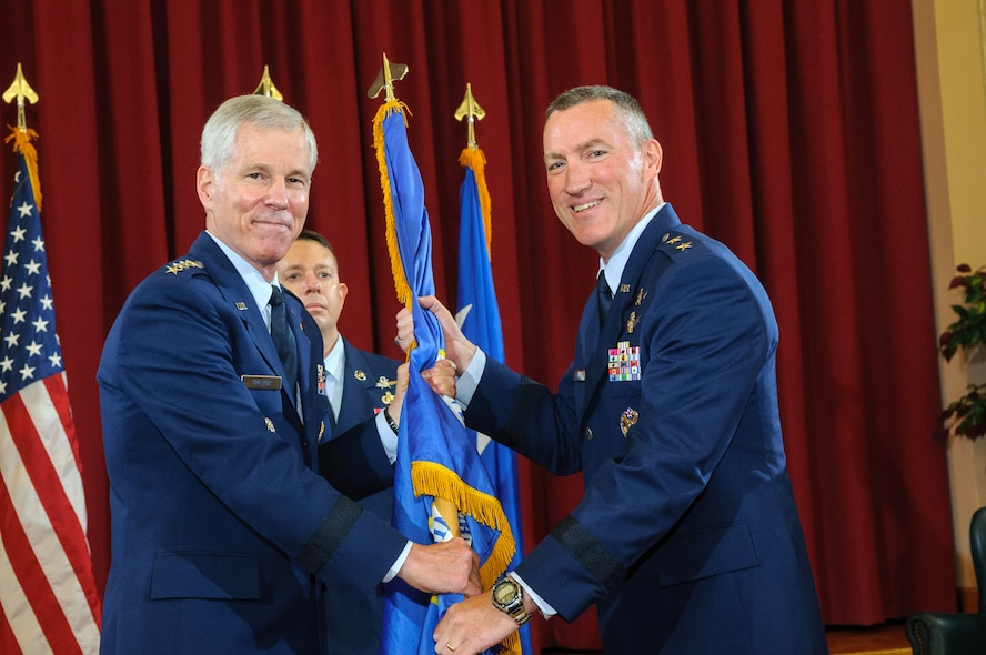 "General William L. Shelton (left), commander of Air Force Space Command, passes the 24th Air Force guidon to Maj. Gen. Burke E. ""Ed"" Wilson after Maj. Gen. James K. ""Kevin"" McLaughlin (not pictured) relinquished command, at Joint Base San Antonio - Lackland, Texas, July 31. Wilson was previously the deputy commander of Air Forces Cyber from September 2011 through June 2013. (U.S. Air Force photo by William Belcher)"