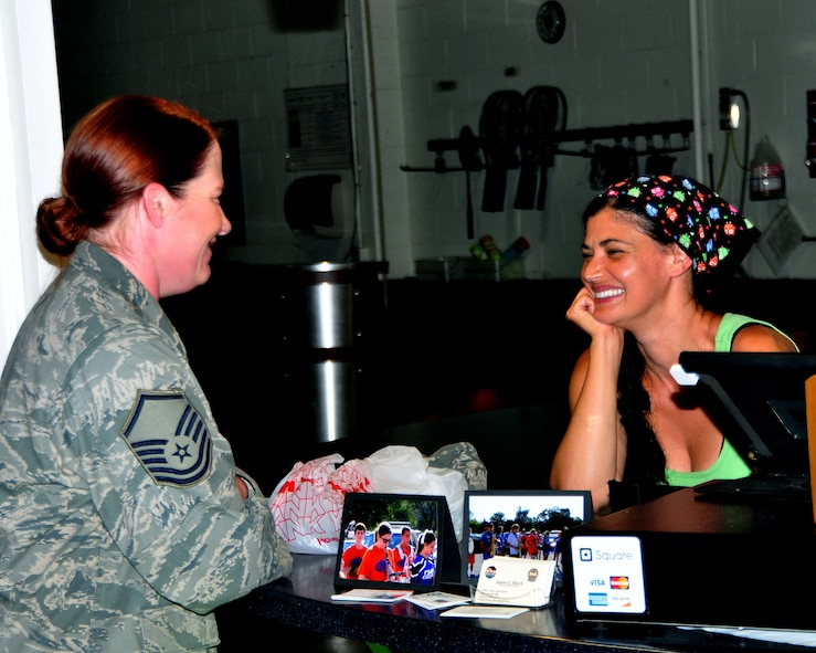 U.S Air Force Master Sgt. Jacqueline Adair, U.S. Strategic Command computer networking specialist, shares a laugh with Ayten Hooper, Smoothalicious owner and operator, June 6 at the Offutt Field House. Smoothalicious offers a variety of sandwiches, salads and their specialty, smoothies. (U.S. Air Force photo by D.P. Heard/Released)