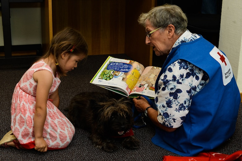 Lucia Padillabarg (left) and Anka Jessie (right), read a book to Pepper, a Red Cross Morale Dog, in the library at Spangdahlem Air Base, Germany, July 31, 2014.  Pepper helps the Red Cross by meeting with patients at hospitals like Landstuhl Regional Medical Center in an effort to reduce stress and raise morale. (U.S. Air Force photo by Airman 1st Class Kyle Gese/Released)