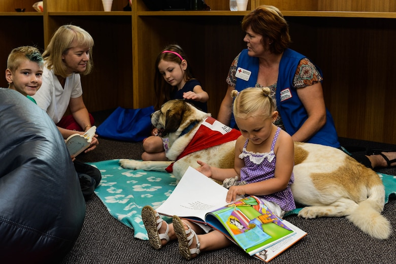 Children meet with Rocky, a Red Cross Morale Dog, in the library at Spangdahlem Air Base, Germany, July 31, 2014. The Red Cross dogs help the Chaplain Corps by meeting with people who suffer from traumatic events or feel stressed. The Red Cross Dogs Aim to reduce stress and increase morale in the community. (U.S. Air Force photo by Airman 1st Class Kyle Gese/Released)