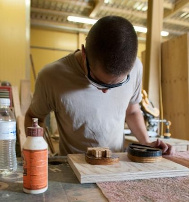 Army Spc. David Beachey from Highland, Ind., who serves with the 1413th Engineer Company, Indiana National Guard, examines his work in the woodshop at Kandahar Airfield, Afghanistan, July 26, 2014. Beachey, the primary sign maker, works for Army Spc. Keith Harris, the shop's leader. U.S. Army photo by Spc. Ariel J. Solomon
