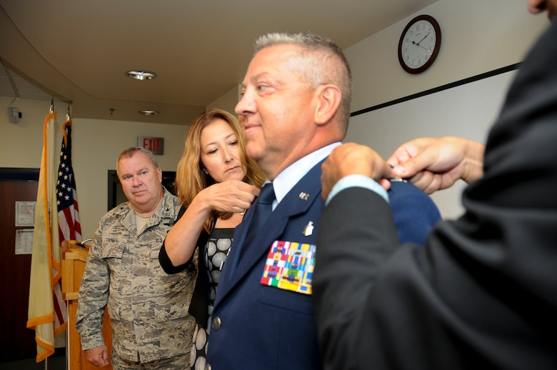Newly promoted Col. Scott Blum, 108th Medical Group commander, stands proudly as his wife, Patricia, and son, Tyler, pin colonel rank on his service dress coat at his promotion ceremony at Joint Base McGuire-Dix-Lakehurst, N.J., July 7, 2014. (U.S. Air National Guard photo by Senior Airman Kellyann Novak/Released)