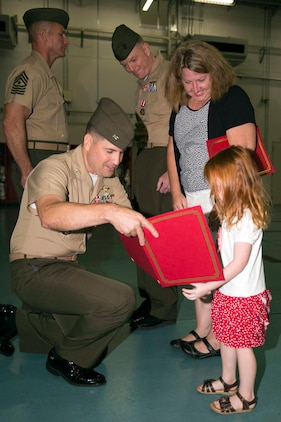 Col. Robert Boucher, station commanding officer, presents Shelby Walker, daughter of Lt. Col. James Walker the station airfield operations officer, with a certificate of appreciation during Walker's retirement ceremony July 25, 2014, aboard Marine Corps Air Station Iwakuni, Japan. Walker retired after 27 years of service in the Marine Corps.
