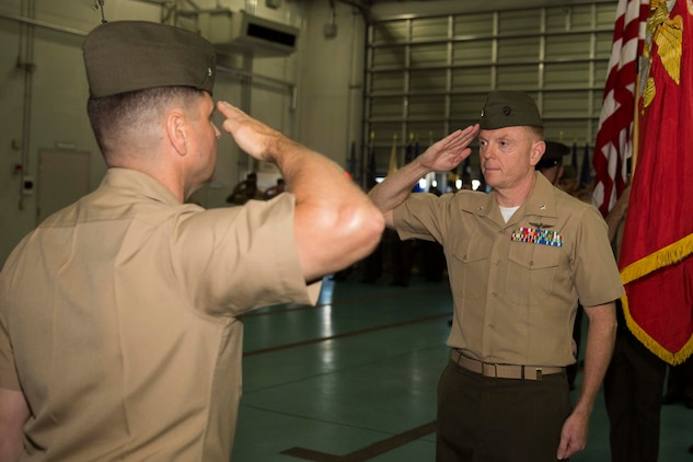 Col. Robert Boucher, station commanding officer, left and Lt. Col. James Walker, station airfield operations officer, salute the National Anthem during Walkers retirement ceremony, July 26, 2014, aboard Marine Corps Air Station Iwakuni, Japan. Walker retired after 27 years of service in the Marine Corps.